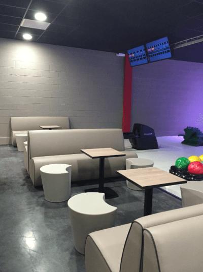 aménagement bowling banquettes grises et tables design